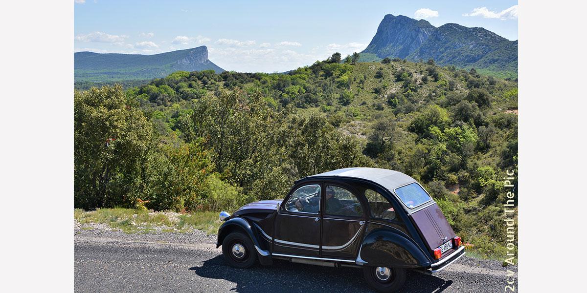 Photo de la 2cv devant la vallée du Pic saint Loup et le plateau de l'Hortus