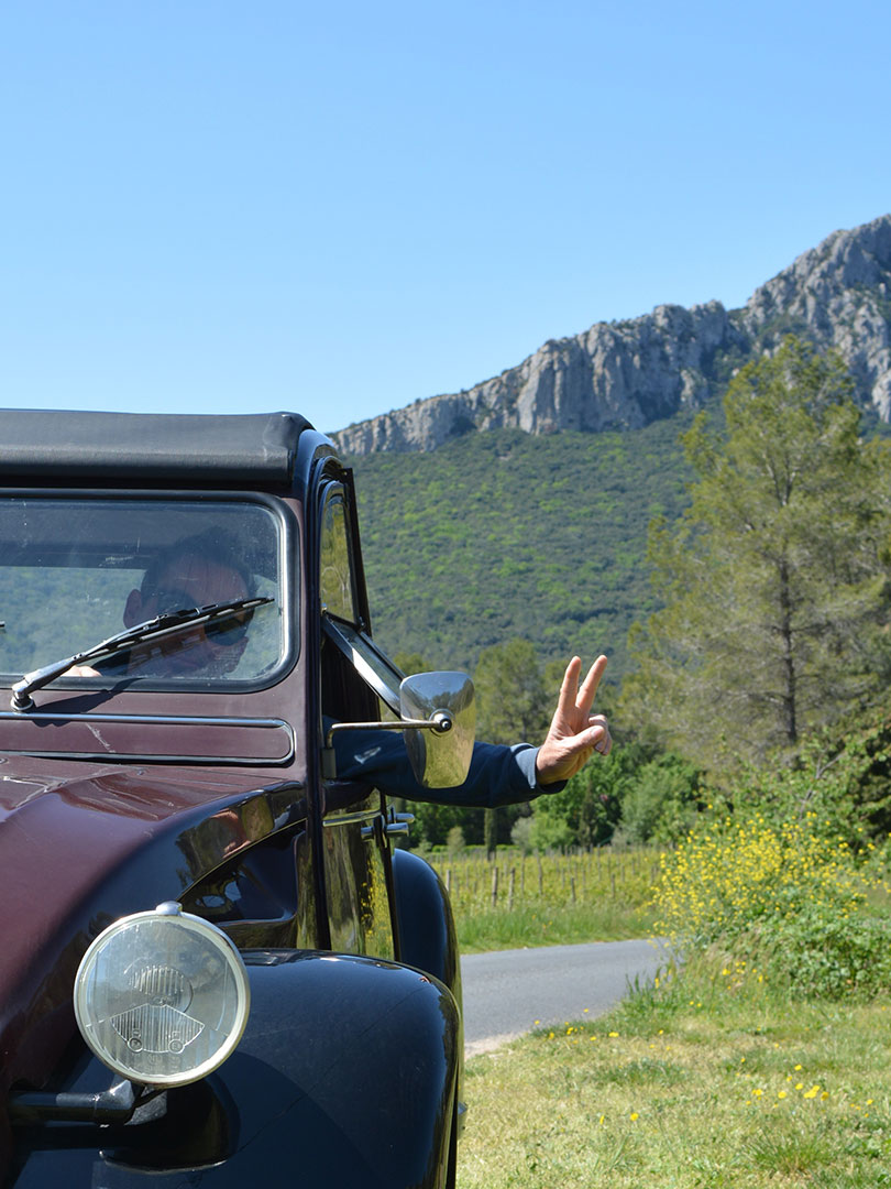 Photo de Christian à bord de sa 2cv Charleston devant le pic Saint Loup